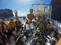 Asiatisk dykinstruktör som ger en dykförhandsmöte till en grupp av turister royaltyfria bilder