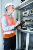 Asiatisk elektriker på panelen på konstruktionsplats Royaltyfri Fotografi