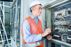 Asiatisk elektriker på panelen på konstruktionsplats Arkivbild