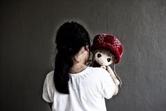 Asiatisk ensam flicka med ledsen gest för docka Pennalism och isolering Royaltyfri Fotografi