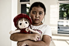 Asiatisk ensam flicka med ledsen gest för docka Pennalism och isolering Royaltyfri Foto