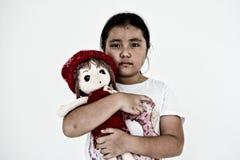 Asiatisk ensam flicka med ledsen gest för docka Pennalism och isolering Royaltyfria Bilder