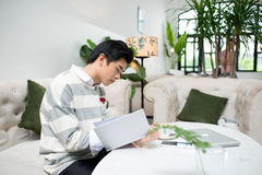 Asiatisk entreprenörläsebok under kaffeavbrott royaltyfri fotografi