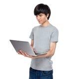 Asiatisk för bruksanteckningsbok för ung man dator Arkivfoto