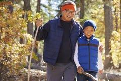 Asiatisk fader och son som fotvandrar i en skog som omfamnar Royaltyfri Fotografi