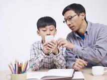 Asiatisk fader och son som spelar med mobiltelefonen Fotografering för Bildbyråer