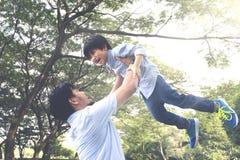 Asiatisk fader som lyfter hans son Arkivbilder