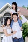 Asiatisk familj framme av det nya huset Arkivfoto