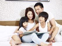 Asiatisk familj med läseboken för två barn i sovrum royaltyfri fotografi