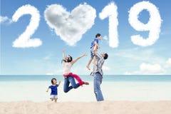 Asiatisk familj med numret 2019 på stranden fotografering för bildbyråer