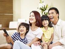 Asiatisk familj med två barn som hemma håller ögonen på TV fotografering för bildbyråer