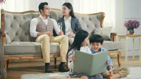 Asiatisk familj med två barn som hemma kopplar av stock video