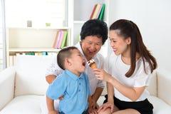Asiatisk familj som äter glass. arkivfoton