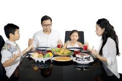 Asiatisk familj som ber tillsammans för att ha mål arkivfoton