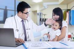 Asiatisk familj som besöker doktorn Arkivbilder