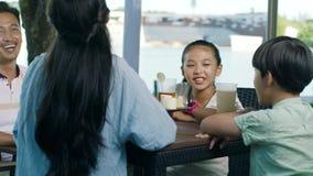Asiatisk familj som dricker & talar på utomhus- placering som tycker om lycklig familjtid i ultrarapid lager videofilmer