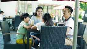 Asiatisk familj som dricker & talar på utomhus- placering som tycker om lycklig familjtid i ultrarapid arkivfilmer