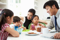 Asiatisk familj som har frukosten, för maken går att arbeta Arkivbilder
