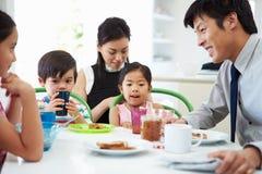 Asiatisk familj som har frukosten, för maken går att arbeta Royaltyfri Foto