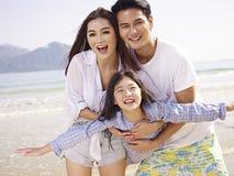Asiatisk familj som har gyckel på stranden fotografering för bildbyråer