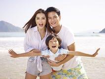 Asiatisk familj som har gyckel på stranden arkivfoton