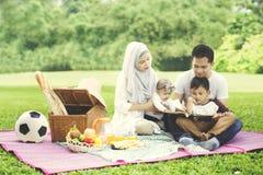 Asiatisk familj som har picknick med en bok Royaltyfria Bilder