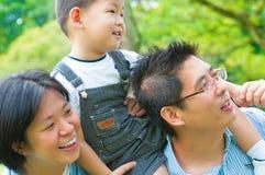 Asiatisk familj som har utomhus- gyckel Arkivbild