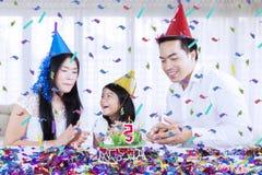 Asiatisk familj som hemma firar en födelsedag arkivbild