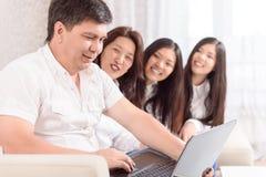 Asiatisk familj som hemma sitter royaltyfria foton