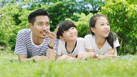 Asiatisk familj som ser upp & ler, när ligga på magen Royaltyfria Foton