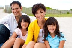 Asiatisk familj som skrattar och spelar på stranden Arkivfoto