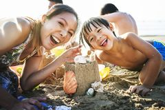Asiatisk familj som spelar på stranden arkivbild