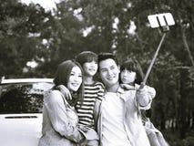Asiatisk familj som tar en selfie under tur royaltyfri fotografi