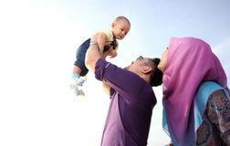 Asiatisk familj som tycker om kvalitets- tid på stranden Arkivfoto