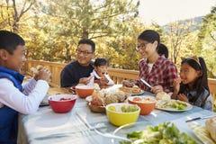 Asiatisk familj som utanför äter på en tabell på ett däck i en skog royaltyfri bild