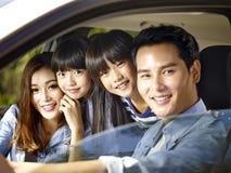 Asiatisk familjridning i en bil fotografering för bildbyråer