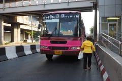 Asiatisk farmor som går till bussen nummer 39 Arkivfoton