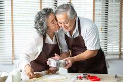 Asiatisk farmor som kysser farfadern medan deras stekheta kakor royaltyfri fotografi