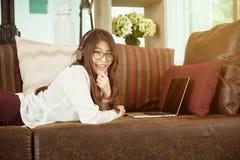 Asiatisk flicka för affär som lutar och använder en bärbar dator på soffan, person arkivbilder