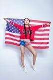 Asiatisk flicka för Hipster i tröja med den hållande amerikanska flaggan för USA ord som isoleras på grå färger Royaltyfri Foto