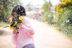 Asiatisk flicka för ung lycklig skönhet med skjortan för sommar för vattenvapen den bärande i den Songkran festivalen - vatt royaltyfri fotografi