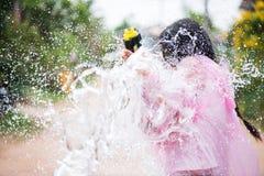 Asiatisk flicka för ung lycklig skönhet med skjortan för sommar för vattenvapen den bärande i den Songkran festivalen - vatt arkivfoton