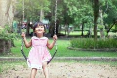 Asiatisk flicka för barn som har gyckel som spelar gunga Arkivfoton