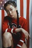 Asiatisk flicka i amerikansk patriotisk dräkt med flätade trådar som ser kameran med oss flagga på bakgrund Royaltyfria Bilder