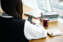 Asiatisk flicka i coworking användande trådlös internetuppkoppling och smartphone i kafé Royaltyfri Bild