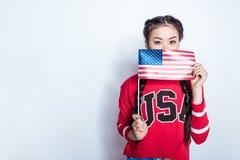 Asiatisk flicka i hållande amerikanska flaggan för patriotisk dräkt och se kameran Arkivbilder