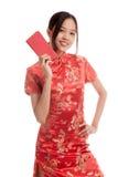 Asiatisk flicka i kinesisk cheongsamklänning med det röda kuvertet Royaltyfri Fotografi