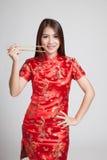 Asiatisk flicka i kinesisk cheongsamklänning med pinnar arkivbilder
