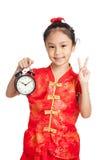 Asiatisk flicka i kinesiskt tecken för seger för cheongsamklänningshow med A.C. Royaltyfria Bilder
