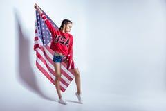 Asiatisk flicka i röd tröja med USA ordet som poserar med amerikanska flaggan som isoleras på grå färger, 4th juli - självständig Arkivfoto
